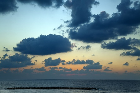 Spectacular color-changing dramatic cloudy sky over the mediterranean sea, very close to the Tel-Aviv beach, as indicated by the breakwater. photo