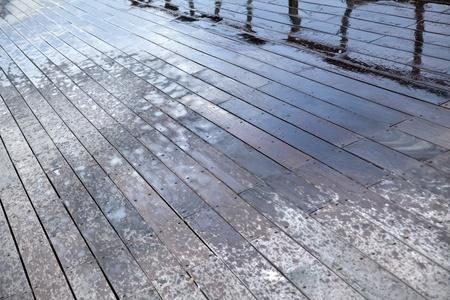 Wooden deck floor of a boardwalk, water sprayed by ricochets splashed off of waves breaking against the boardwalk Stock Photo - 19055257