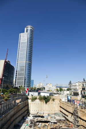 Wide-angle view of a construction site at its early stages of foundation construction, with a tall skyscraper in the background.