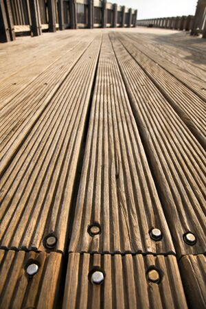 diminishing: A wooden deck footpath in the sunlight, diminishing pespective. Stock Photo