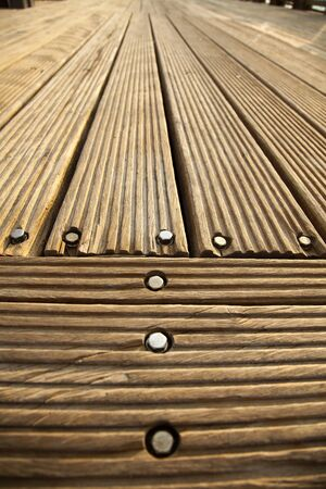 diminishing: A wooden deck floor in the sunlight, diminishing pespective, very wide angle.