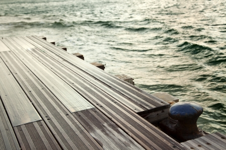 inclement weather: A rusty anchorage on a boat dock, defocused green sea in the background. Inclement weather. Stock Photo