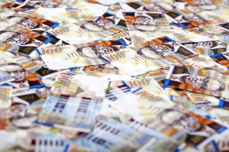 A high angle view of a very large amount of 100 NIS (New Israeli Shekel) money notes spreaded in a messy manner. Very shallow depth of field. Stock Photo - 18933842