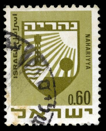 official symbol: A stamp from Israel, depicting the official symbol of the city of Nahariyya. Nahariyya is the most northern city on the Israeli mediterranean coast. Isolated on black background. Stock Photo