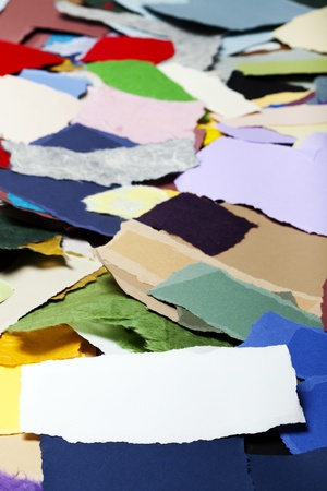 Torn long white fiber paper on the background of a large group of torn pieces of paper in a variety of colors. Good as copy space for text. photo