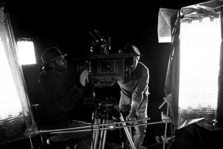 film crew: Tel-Aviv, Israel - February 3rd, 2012: Cinematographer and first assistant camera (focus puller) sitting on a camera dolly at work on a soundstage, surrounded by the lighting setup.