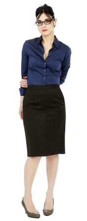 An adult (early 30s) black haired caucasian woman, wearing a blue buttoned shirt, a dark gray skirt  looking at the camera with a somewhat timid expression and posture. Isolated on white background.