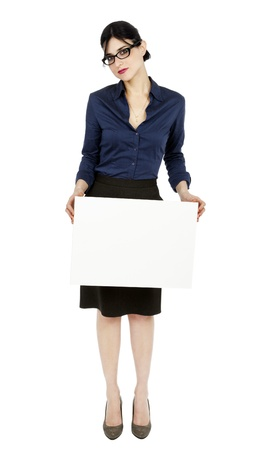 early 30s: An adult (early 30s) black haired caucasian woman wearing a blue buttoned shirt and a dark gray skirt, holding a blank sign in front of her while looking at the camera serious expression. Isolated on white background.  Stock Photo