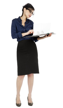 early 30s: An adult (early 30s) black haired caucasian woman wearing a blue buttoned shirt and and a dark gray skirt, holding a ring binder folder and flipping a pagel in the document. Isolated on white background.