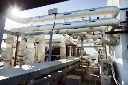 This complex pipes & valves system is located on the roof of an office building, and is part of the water supply system of the HVAC commercial air-conditioning of the building.