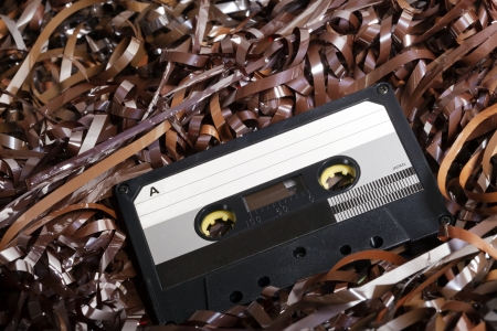 Black recordable plastic audio cassette resting on a large amount of magnetic audio tape  photo