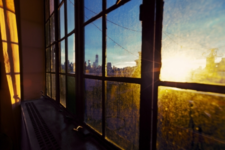 One World Trade Center (aka Freedom Tower) and Lower Manhattan skyline seen through defocused window back lit by afternoon yellow sun on a rooftop West Village apartment. Stock Photo