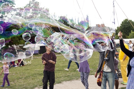 optimisim: Berlin, Germany - June 10th, 2012: A group of young adults making giant soap bubbles on an early summer Sunday afternoon at Mauerpark, with the flea market in the background. Editorial