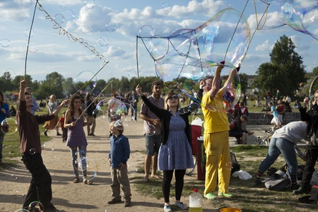 optimisim: Berlin, Germany - June 10th, 2012: A group of people making giant soap bubbles on an early summer Sunday afternoon at Mauerpark, with the parks crowd scattered around them, some spectating.