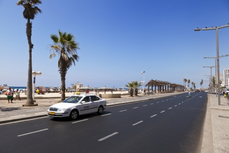 Tel-Aviv, Israel - August 18th, 2012: A taxi driving through the street that stretches along the beach in Tel-Aviv on a hot summer day. Pedestrians on their way to the beach full with people can be seen in the background. Editorial