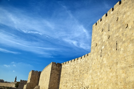 The surrounding wall of the old city of Jerusalem beneath a spectacular cloudy blue sky  Stock Photo