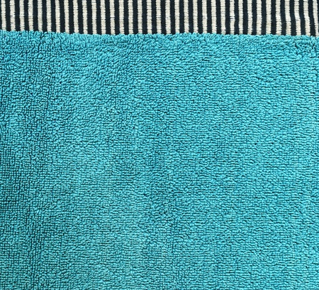 High resolution close up of aqua cotton fabric with a zebra crossing black & white line crossing it horizontally. photo