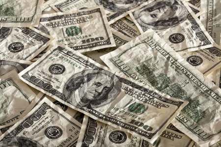 contrasty: A high angle view of a very large amount of crumpled 100 US$ money notes in a bulky mess, with warm & contrasty lighting. Stock Photo