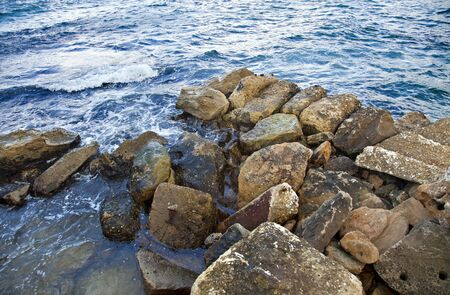 invading: A pile of rocks compiles a land tongue, invading sea waters territory.  Stock Photo
