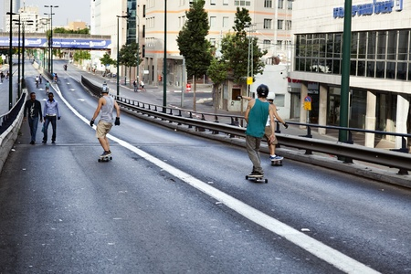 Tel-aviv, Israel - October 8th, 2011: Day of Atonement (Yom Kippur) in Israel. A group of young skateboarders sliding down the Karlibach bridge in Tel-Aviv with their back to the camera, while two man are going the opposite way. Many more children on bicy