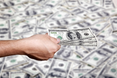 Close up of the right hand of an adult man holding three 100 US$ money notes, in the gesture of giving over a blurred background of a large amount of identical bills.
