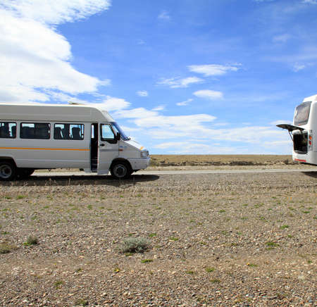 A minibus and a bus parked on the side of the rural road in Patagonia, South America. photo