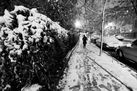 Lone woman walking on the snow covered pavement of a Harlem street on a freezing snowstorm night. Stock Photo