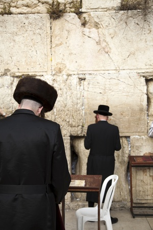 Three orthodox Jewish young adult pressed in prayer against the wailing wall in the old city of Jerusalem. photo