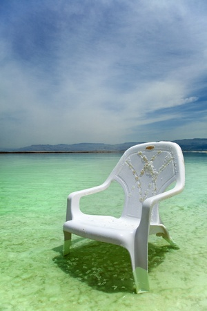A lone salt covered plastic easy chair in the shallow waters of the world famous Dead Sea, Israel. photo