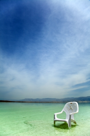 easy chair: A lone salt covered plastic easy chair in the shallow waters of the world famous Dead Sea, Israel.