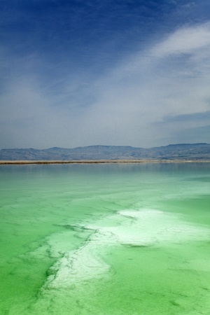 sun  soaked: A look into and through the clear green water of the world famous Dead Sea, which under its surface a large salt covered rock can be seen
