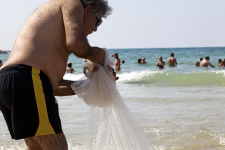 Tel-Aviv, Israel - August 18th, 2012: A mature man pulling a fishing net out of the water on the beach on a hot summer day.