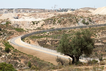 apartheid: A view of the wall of separation deviding between Palestine and the occupied Palestinian territories in Israel, with an Israeli settlement on occupied territories in the background.