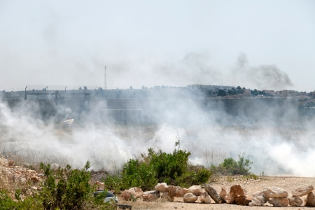 Bilin, Israel - May 17th, 2013: A cloud of tear gas flying in the wind by the wall of separation between Palestine and Israel, with Israeli soldiers behind the wall.