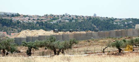 Bil'in, Palestine - May 17th, 2013: Israeli army jeeps and soldiers standing behind the wall of separation, with Israeli settlements on occupied Palestinian territories in the background.