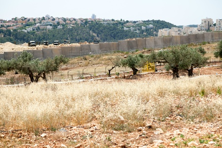occupied: Bilin, Palestine - May 17th, 2013: Israeli army jeeps and soldiers standing behind the wall of separation, with Israeli settlements on occupied Palestinian territories in the background.