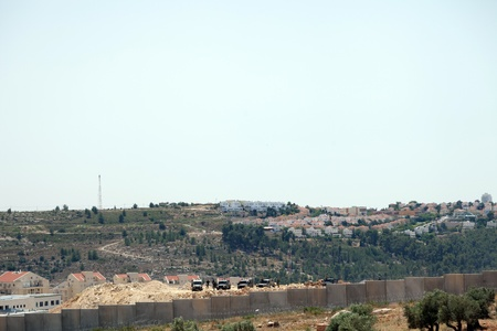 apartheid: Bilin, Palestine - May 17th, 2013: Israeli army jeeps and soldiers standing behind the wall of separation, with Israeli settlements on occupied Palestinian territories in the background.