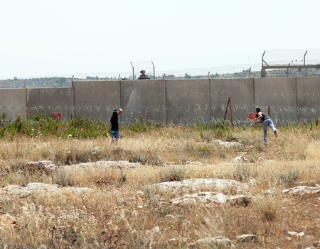 middle east fighting: Bilin, Palestine - May 17th, 2013: Two Palestinian youths throwing rocks towards the Israeli army force standing behind the wall of separation that is between them. This is part of the weekly demonstration taking place in the village of Bilin. Editorial