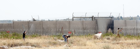 middle east fighting: Bilin, Palestine - May 17th, 2013: Three Palestinian youths throwing rocks towards the Israeli army force standing behind the wall of seperation that is between them. This is part of the weekly demonstration taking place in the village of Bilin. Editorial