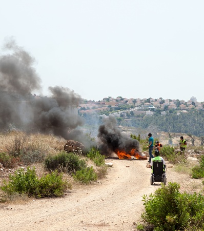 apartheid: Bilin, Palestine - May 17th, 2013: People walking by tires burning on the road leading to the wall of separation in the west bank, in the middle of a protest against the Israeli occupation of Palestine. Editorial