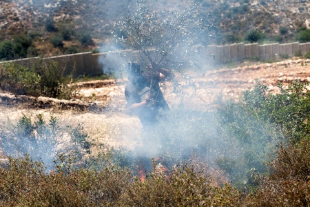 Bilin, Palestine - May 17th, 2013: A Palestinian person wearing a gas mask trying to put out fire caused by gas mask cannisters landings in the field by the wall of separation in the middle of a conflict with the Israeli army at a protest against the occ Editorial