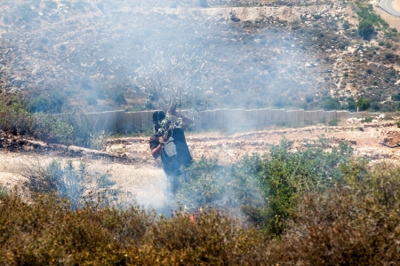 occ: Bilin, Palestine - May 17th, 2013: A Palestinian person wearing a gas mask trying to put out fire caused by gas mask cannisters landings in the field by the wall of separation in the middle of a conflict with the Israeli army at a protest against the occ Editorial