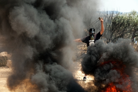 middle east fighting: Bilin, Palestine - May 17th, 2013: A Palestinian protester preparing his slingshot for shooting amongst black smoke coming from burning tires, at a protest against the Israeli occupation.