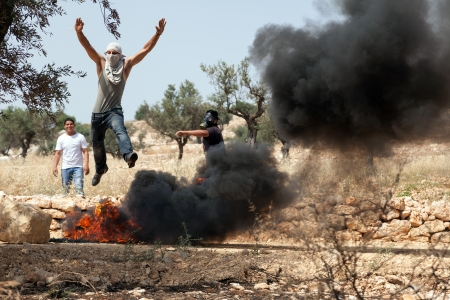 palestinian: Bilin, Israel - May 17th, 2013: A young Palestinian protester jumping over flaming tires at a protest against the Israeli occupation, with his friends watching him. Editorial