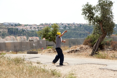 middle east fighting: Bilin, Palestine - May 17th, 2013: A Palestinian protester using his slingshot to shoot a rock at the soldiers on the other side of the wall of separation at a protest against the Israeli occupation. Editorial