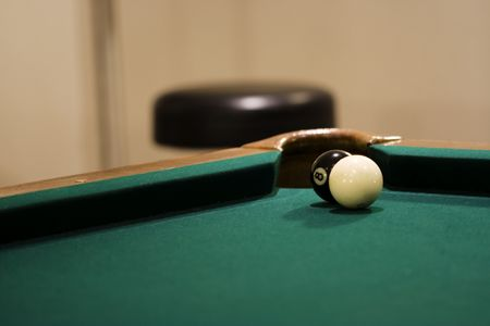 Black eight ball with white cue ball in corner pocket  photo