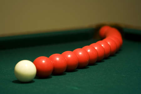 White cue ball with arcing red pool balls photo