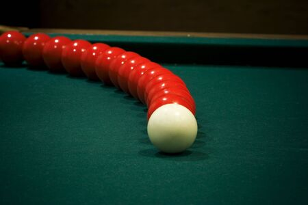 White cue ball in front of arcing red pool balls  photo