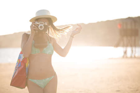 Attractive fit trendy modern hipster woman taking photos with retro vintage film camera.Lifestyle photographer.Summer beach woman taking picture during summer holiday vacation travel Stock Photo