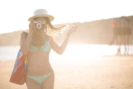 Attraktive fit modische moderne Hipster Frau Fotos mit Retro-Vintage Film camera.Lifestyle photographer.Summer Strand Frau, die Aufnahme während der Sommerferien Urlaub Reise Standard-Bild - 52646798